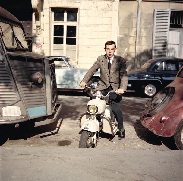 Raymond Depardon - Un moment si doux : Raymond Depardon, Autoportrait au Rolleiflex (posé sur un mur) 1er scooter de marque Italienne « Rumi », avec étiquette de presse sur le garde-boue. Île Saint-Louis. Paris, 1959, 25 x 25 cm © Raymond Depardon / Magnum Photos