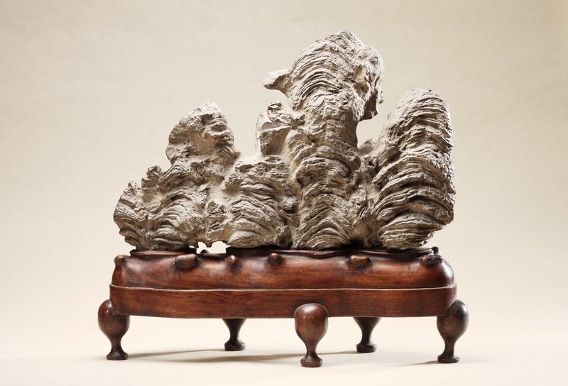 Rochers de lettrés. Itinéraires de l'art en Chine : Montagne miniature. Dynastie Ming, pierre Lingbi en peau de datte, support en bois de rose. Collection Zeng Xiaojun.