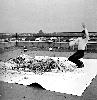 Gutai, l'espace et le temps : Ohara Kaikan. Shimamoto Shôzô créant une peinture en lançant des bouteilles en verre de peinture contre une toile à la deuxième exposition d'art Gutai.  17 novembre 1956, photographie.